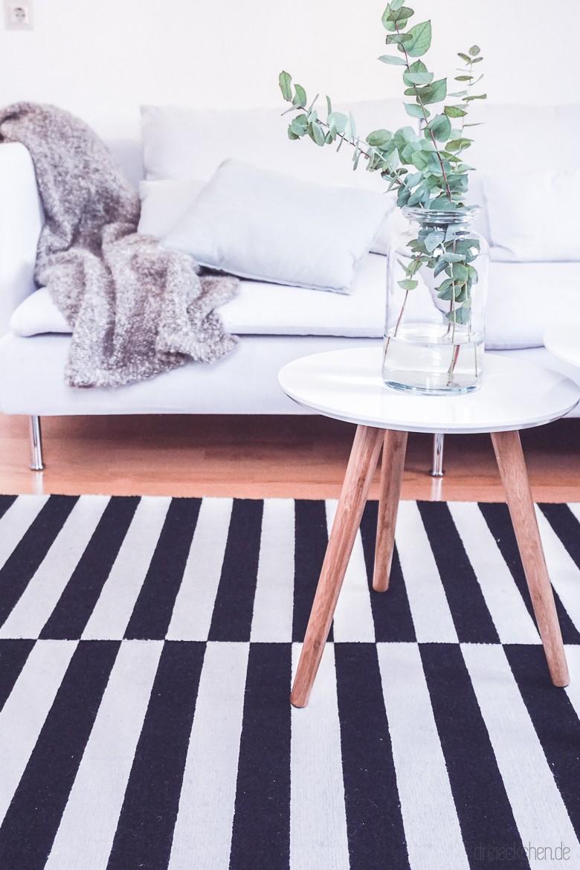 IKEA Couch SÖDERHAMN Finnsta weiß mit Kuscheldecke, Couchtisch mit Eukalyptus in einer Glasvase und IKEA Teppich Stockholm schwarz weiß gestreift