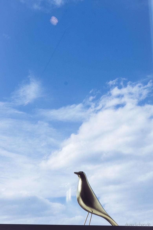 goldener Holzvogel vor blauem Himmel