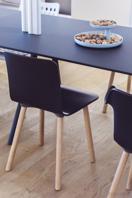 Vitra Holzstühle mit dunkler Sitzfläche am Tisch mit Etagen in hellblau gefüllt mit Walnüssen