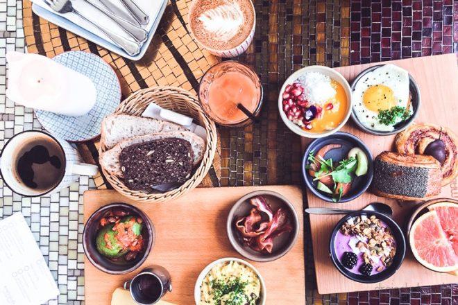 Tisch mit Frühstück: Kaffee, Brot, Spiegelei, Müsli, Porridge, Speck, Avocado