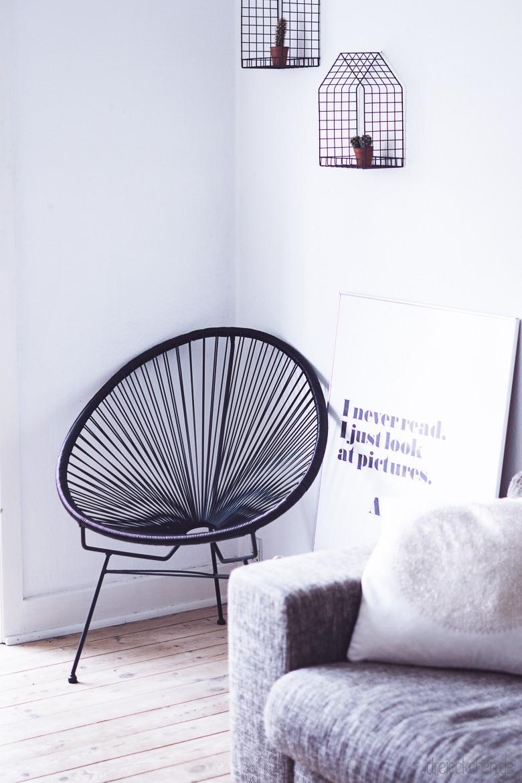 Couch mit schwarzem Acapulco Chair und Typografie-Bild