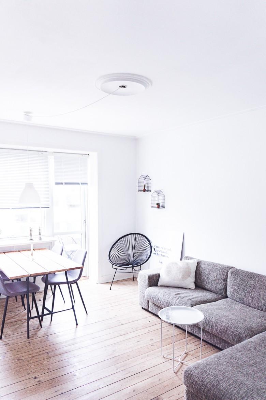 Skandinavisch eingerichtetes Wohnzimmer mit Couch, Tablettisch, Essplatz, Acapulco Chair
