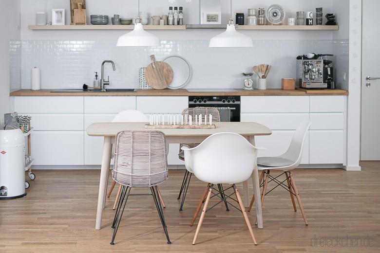 offene Scandi-Küche mit viel weiß und Holz, Essplatz, Vitra Eames Armchair und Hängeleuchten von IKEA